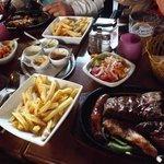 Grigliata di carne con contorno di insalata e patatine