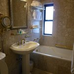 Bathroom tub with window and free standing sink