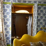 Wallpapered closets + nice robes + yellow velvet sofa