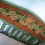 Detalhe  da cabeceira da cama , com flores de de cerâmica.