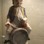 A weird porcelain figure of a soldier sitting on a barrel