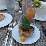Fresh fruit juice served with warm crousants, fresh apricot jam, and plums in a delicious marina