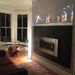 Living room with projected silent films and ballet over the fireplace.