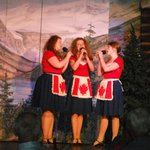 The three female leads singing in their Canadian flag aprons.