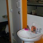 di fronte al letto, lavandino e porta del bagno