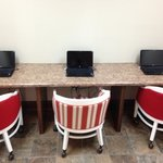 Business center with three computers and wireless printing available