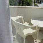small balcony with table and chairs overlooking pool