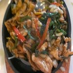 Chicken with 3 peppers on a hot plate