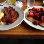 Pancakes with fresh strawberries, eggs, and bacon