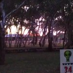 Sunset over the back of the caravan park area looking through an unoccupied unpowered site