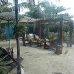 Outdoor patio area with hammocks, cornhole game, bikes, and lockers for dive and snorkel gear