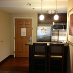 Kitchen area with full size fridge, dish washer and even a 2 stove top with pots and pans.