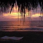 Por do sol na praia, a areia é escura, mas reflete o sol