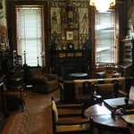 The men's smoking room with an array of interesting collectables such as weapons, flags and armo