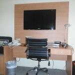Biurko i duży płaski telewizor w pokoju hotelowym,