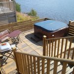 The hot tub and BBQ. There is a table and chairs on the decking behind.