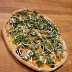 Mediterranean Pizza made with arugula, asparagus,chicken black olives and green onions