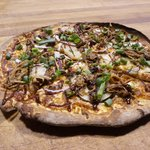 Stompin' Tom Pizza made with Island pulled pork, Island Potatoes, Jalapeño Bacon and red onions.