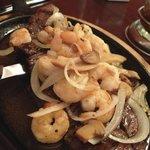 Skirt steak with shrimp, onions and mushrooms.