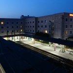 Blick von der Fußgängerüberführung auf Hotel und Bahnhof bei Nacht