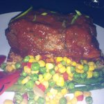 BBQ Sauce Covering the Short Rib over Frozen Peas & Corn