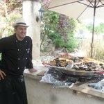 le patron mettant son savoir faire pour une délicieuse paella