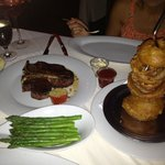 24 oz porterhouse steak with onions rings and asparagus.