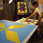 Clay at work in the studio painting a barnquilt