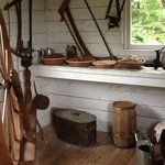 the milk shed contains a spinning wheel and other artifacts