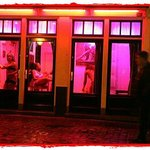 See girls working behind windows to attract men in the Red Light District