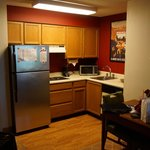 View of the kitchen; fridge, microwave, stovetop, and dishwasher