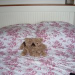 Bed with two cute stuffed teddy bears side-by-side