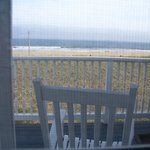 Semi-Private porch with chair in front of room (seen through screen)