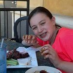 Loving the wings up to her wrists in the sauce!