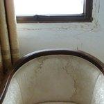 Völlig verdreckter Stuhl unter defektem Fenster
