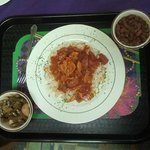 A yummy creole dish over rice with sides of green beans with potatoes and red beans and rice.