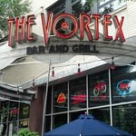 The Vortex Street Entrance Sign Next To Outdoor Seating