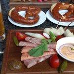 Plate of ham, sausage, pickles with pretzel