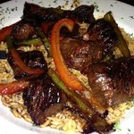 Steak Tips over rice with onions and peppers.
