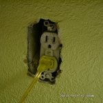 Loft electrical outlet with exposed wires on side of outlet