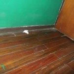 Entrada de la habitación, polvo acumulado y papeles tirados.