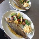 oven roasted whole sea bass with salad and comes with new butter and fresh parsley new potatoes