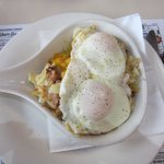 Two over-easy eggs with corned beef hash, potatoes and cheese.