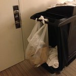 Nice bag of garbage hanging form a cleaning cart in the middle of the hallway at 2:00 am