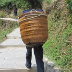 Locals carrying bags for visitors up the path to the hotel