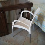 A tatty plastic chair by the desk