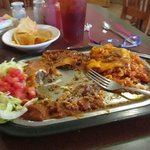 Enchilada plate with blob of cheese removed to the side, dark ikky sauce