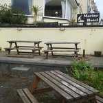 Front of hotel with worn and broken picnic tables etc