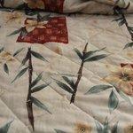 Big hole in dirty bedspread.
