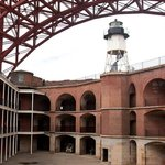 Courtyard view of Fort Point with lighthouse and Golden Gate Bridge.